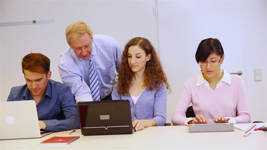 four coworkers looking graphs and data on a lap top